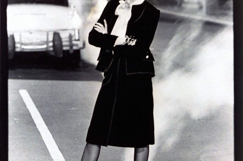 Model Rosie Vela standing with arms crossed in the street in New York City, near a steaming manhole Vogue cover, wearing a black velvet Chanel suit with wrap skirt and a small jacket over white satin blouse, by Belle Saunders for Abe Schrader, 1975. (Guliver Photos/ Getty Images).