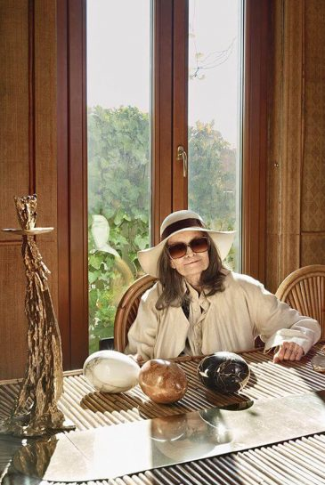 Gabriella Crespi, in her Milan home of 40 years, surrounded by the furniture designs that made her famous, including the Rising Sun table and chairs, a heron sculpture and a 1974 candlestick.